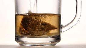 La bolsita de té de la pirámide en taza se vierte sobre el agua hirvienda metrajes