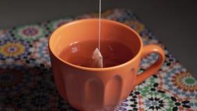 La bolsita de té sumergió en agua caliente almacen de video