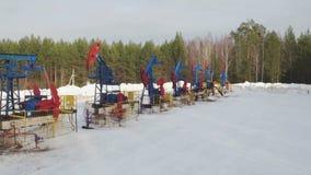 La bomba de aceite industrial de la visión aérea levanta el petróleo crudo de bombeo en campo petrolífero almacen de metraje de vídeo