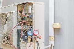La bomba de vacío del técnico evacua y comprobando el acondicionador de aire, foto de archivo libre de regalías