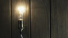 La bombilla ilumina en fondo de madera almacen de metraje de vídeo