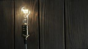 La bombilla ilumina en fondo de madera metrajes