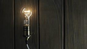 La bombilla ilumina en fondo de madera almacen de video