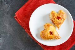 La bonne forme de coeur de lookind durcit sur le plat blanc avec la serviette rouge et Photo libre de droits