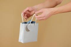 La borsa in bianco del regalo della carta blu con i cuori deride sulla tenuta a disposizione E Fotografia Stock