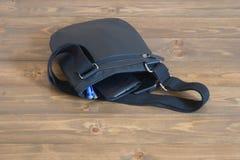 La borsa degli uomini con le cose che si trovano sul pavimento Fotografie Stock