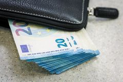 La borsa ed il batuffolo di cuoio neri di contanti 20 euro sono bugia sulla tavola grigia Immagine Stock