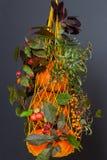 La borsa gialla della maglia in pieno dei tipi differenti zucche, vecchio reticolato decorato con l'autunno si ramifica, feste, a Fotografia Stock Libera da Diritti