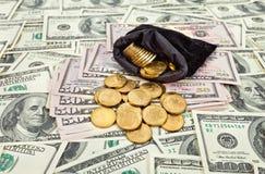 Borsa riempita di monete sopra le banconote degli Stati Uniti Fotografia Stock