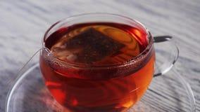 La borsa scende e nuota in una tazza trasparente di vetro con tè nero profumato stock footage