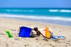 La borsa, suncream, scherza i giocattoli sulla spiaggia Immagini Stock Libere da Diritti