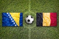 La Bosnia-Erzegovina contro Bandiere del Belgio sul campo di calcio Fotografia Stock