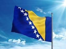La Bosnia-Erzegovina inbandiera l'ondeggiamento nel cielo blu Immagine Stock