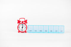 La boîte hebdomadaire de pilule et l'horloge rouge montrent le temps de médecine Image stock
