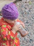 La botella come al bebé en el casquillo Imagen de archivo
