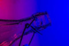 La botella con las gotitas con color se enciende en fondo Fotos de archivo