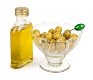 La botella de aceite de oliva con las aceitunas verdes regó con aceite Imagen de archivo libre de regalías