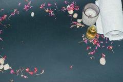 La botella de aceite esencial del aroma con la vela, pétalo florece Fotos de archivo