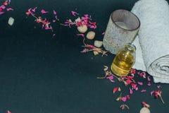 La botella de aceite esencial del aroma con la vela, pétalo florece Imagen de archivo