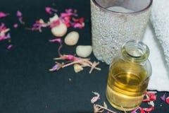 La botella de aceite esencial del aroma con la vela, pétalo florece Foto de archivo libre de regalías