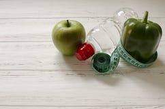La botella de agua, la manzana verde y la pimienta, centímetro en blanco cortejan Foto de archivo