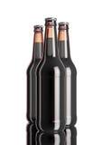 La botella de cerveza en la tabla blanca del fondo y del espejo del softbox Imagen de archivo