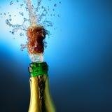 La botella de champán con salpica Imagen de archivo