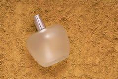 La botella de cristal de perfume está en la arena imagen de archivo