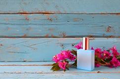 La botella de perfume del vintage al lado de la buganvilla florece en la tabla de madera Imagen de archivo