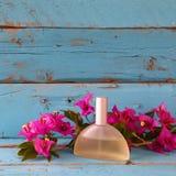 La botella de perfume del vintage al lado de la buganvilla florece en la tabla de madera Imagen entonada Imagen de archivo libre de regalías