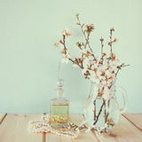 La botella de perfume fresca del vintage al lado de la primavera blanca florece en la tabla de madera imagen filtrada vintage Fotografía de archivo libre de regalías