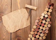 La botella de vino formó corchos, el sacacorchos y el trozo de papel Foto de archivo libre de regalías