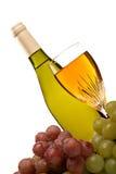La botella de vino y el vidrio de vino con las uvas aislaron Imagen de archivo