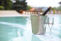 La botella del champán del cubo de hielo y dos vidrios acercan a la piscina Foto de archivo libre de regalías