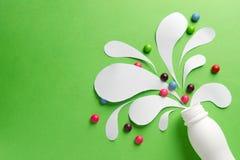 La botella del yogur con salpica y las vitaminas Fotografía de archivo