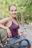 La botella feliz del asimiento de la mujer de agua fría y se relaja Fotografía de archivo libre de regalías