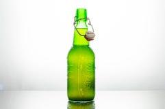 La botella verde aislada de cerveza de Grolsch en un fondo blanco se encendió de detrás Fotos de archivo