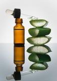 La bottiglia ambrata con la foglia di vera dell'aloe incide i pezzi ed il contagoccia Fotografia Stock