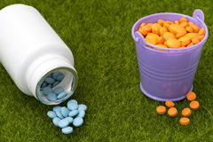 La bottiglia bianca delle pillole e dei secchi blu ha riempito di compresse arancio Immagini Stock