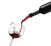 La bottiglia che versa il vino rosso in vetro con spruzza Fotografie Stock Libere da Diritti