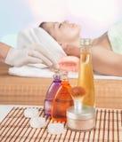 La bottiglia cosmetica dell'olio aromatico di massaggio è sulla tabella cosmetica immagine stock libera da diritti