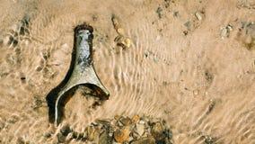 La bottiglia del coccio si trova sulla banca del fiume Fotografia Stock Libera da Diritti