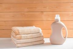 La bottiglia del detersivo vicino ad un mucchio degli asciugamani fotografia stock libera da diritti