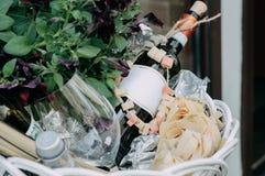 La bottiglia del vino rosso, il vetro ed i fiori non aperti del fiore nel canestro Fotografia Stock