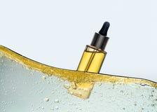 La bottiglia dell'olio cosmetico giallo nell'onda dell'emulsione dell'olio Immagini Stock