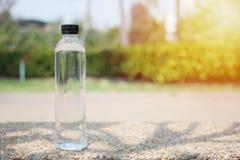 La bottiglia di acqua bevente riposa su un'arenaria immagine stock