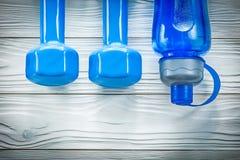 La bottiglia di acqua delle teste di legno sul bordo di legno mette in mostra il concetto di addestramento Fotografie Stock