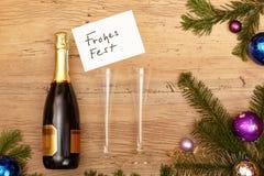 La bottiglia di Champagne, carda le feste felici, i vetri del champagne e l'abete Fotografia Stock Libera da Diritti