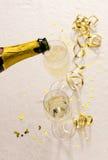 La bottiglia di Champagne riempie i vetri Fotografia Stock