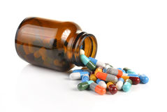 La bottiglia di pillola che rovescia le pillole sopra per sorgere ha isolato su un BAC bianco Fotografia Stock Libera da Diritti